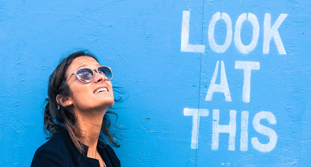Portrait of a model wearing sunglasses next to a blue wall