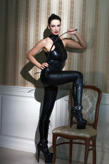 Woman in latex catsuit with whip