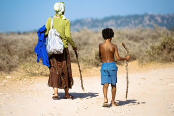 An old woman and a young boy walking along the dusty road