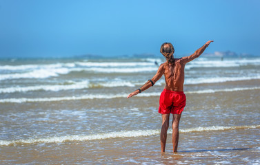 An elderly swimmer standing in the waves of the sea