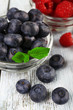 Glass bowls of raspberries and blueberries on wooden background