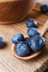 Wooden bowl of blueberries on cutting board on wooden