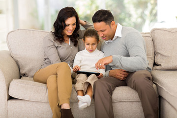family using tablet computer at home