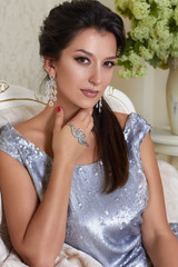 Woman wearing evening dress silver earrings sitting on couch