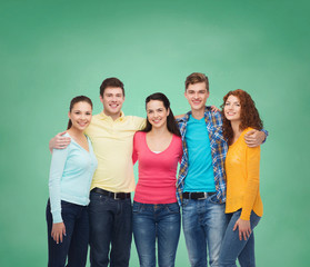group of smiling teenagers over green board