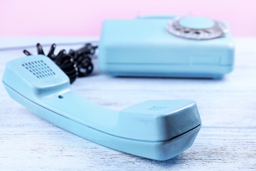 Retro turquoise telephone on wooden table, close up