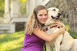 Woman with visual impairment hugging  her service dog