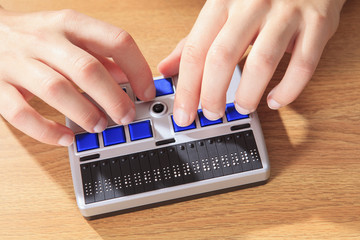 Student with visual impairment using her Braille display