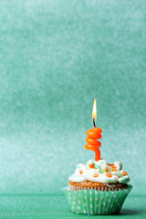 Delicious birthday cupcake on green background
