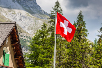 Swiss flag - national symbol of Switzerland with Alps in backgro