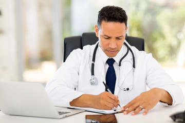 male medical doctor writing reports
