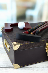 Golf set in suitcase on table on bright background