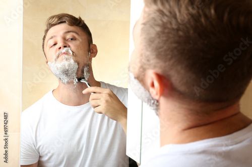 canvas print picture Young man shaving his beard in bathroom