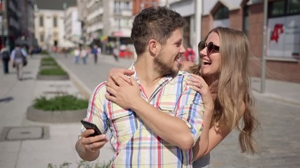 Happy woman surprises waiting man by covering his eyes