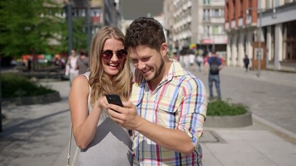 Attractive couple taking self-portrait with phone in a city