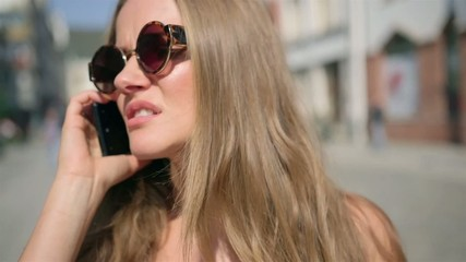 Portrait of upset woman talking on phone  in a city street
