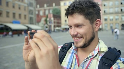 Young man with beard taking picture with cellphone in a city.