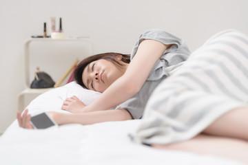 スマートフォンを持って寝落ちした女性