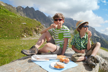 Two boys have got picnic on stone in mountains