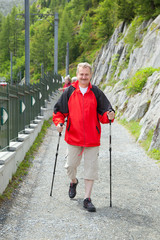 The elderly man hikes on trail in Alps