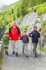 The grandfather, grandmother and two boys walk in mountain