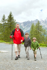The grandfather and two boys trakking on mountain trail