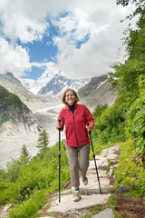 Smiling woman runs on mountain trail against glacier