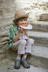 The small boy sits on the stone steps and eats pizza