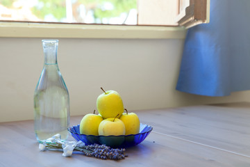 Yellow fresh apples on blue plate and bottle of water