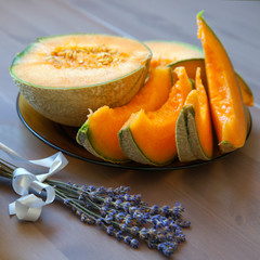 Pieces of cavaillon melon and lavender bunch on wood table
