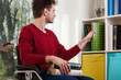 canvas print picture - Disabled man cleanig up a bookshelf