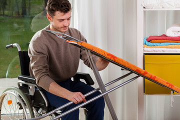 Disabled man setting up an iron board