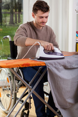 Disabled man ironing