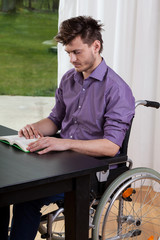 Man on wheelchair reading a book