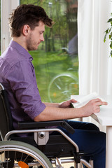 Disabled man at home reading a book