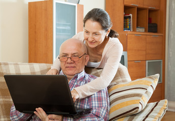 man and woman   on  couch with  laptop