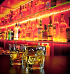 glasses of whiskey with ice on bar table on warm atmosphere