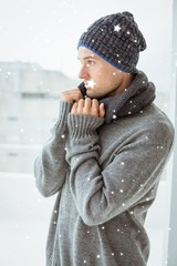 Composite image of handsome man in warm clothing