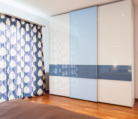 Blue and white wardrobe in bedroom