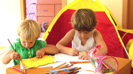 calm children sketching on paper in home interior