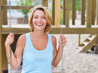 Happy beautiful woman having fun on a swing.