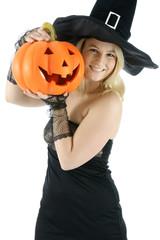 Hexe zu Halloween hält Kürbis
