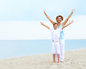 Happy mother and son standing on the beach.