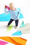 Mały chłopiec  trzyma w dłoni papierowy samolot