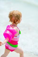 Baby girl running on beach