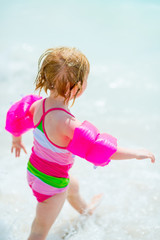 Baby girl running at seaside