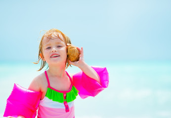 Portrait of baby girl listening sound of sea in shell on beach