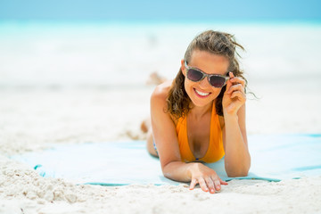 Portrait of smiling woman in sunglasses laying on sea coast