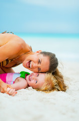 Portrait of mother and baby girl playing on beach