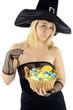 Hexe zu Halloween hält Süßes und Saures